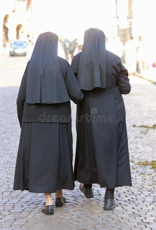 Two sisters with black dresses and a veil walking in the city. Two sisters with black dresses and a veil to cover the hair walking in the european city stock photo