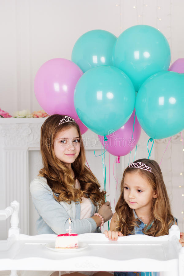 Two sisters are celebrating birthday with cake. Two cute girls sisters are celebrating birthday in a studio with cake and blue and pink balloons royalty free stock photos