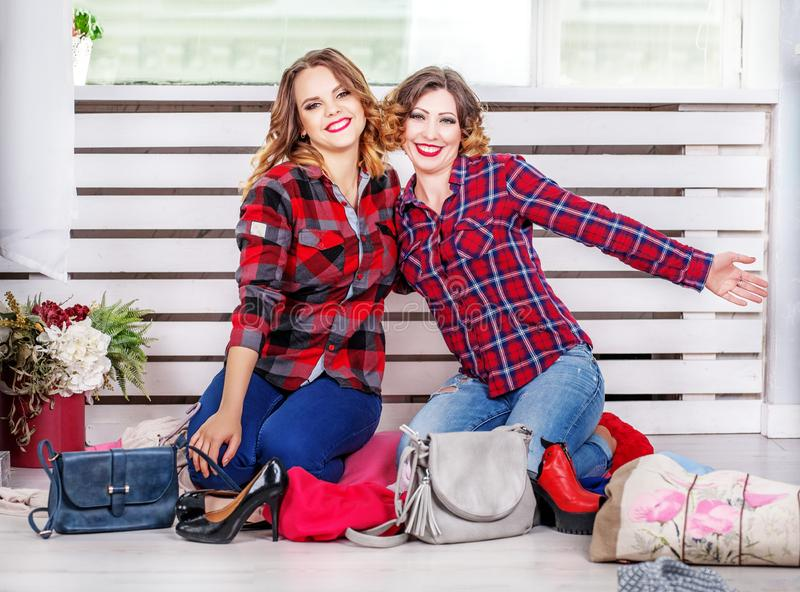Two sisters choose clothes of her wardrobe. The concept of fashi. On, style, friendship stock images