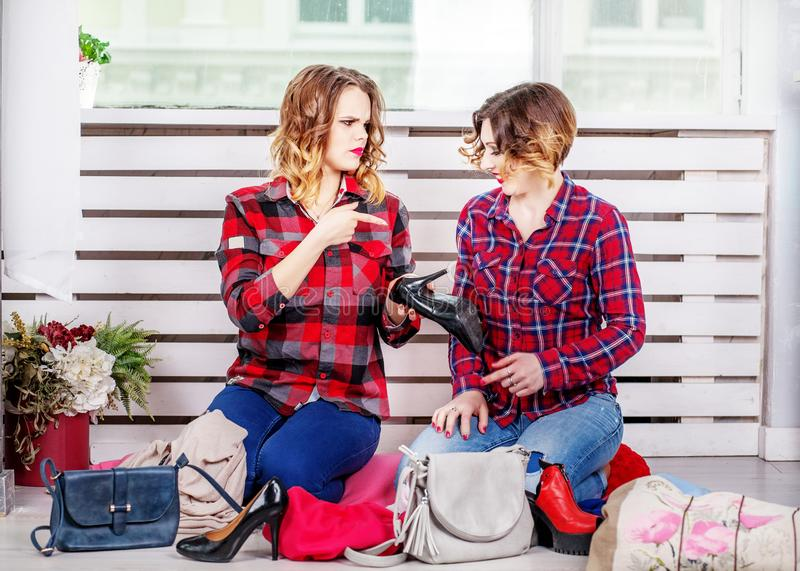 Two sisters choose her wardrobe of shoes. The concept of fashion. Style, friendship stock photography