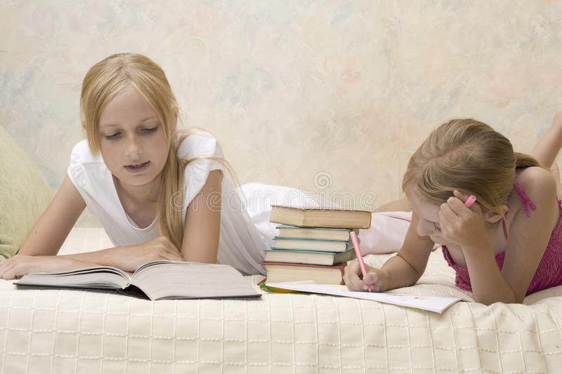 Two sisters do homework royalty free stock photos