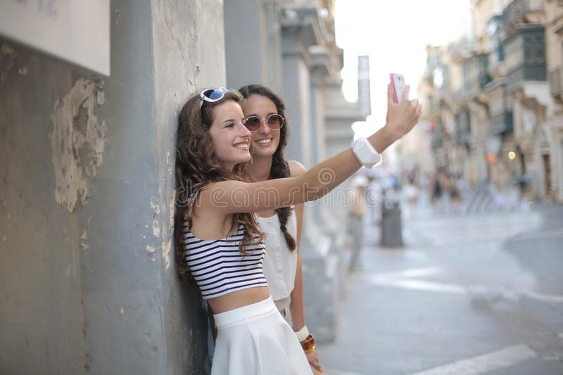 Two sisters doing a selfie. Together stock photos