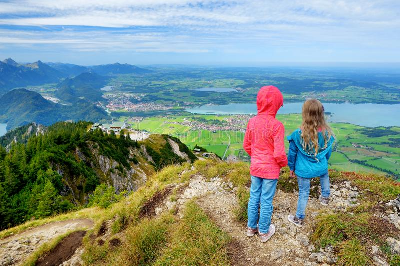 Two sisters enjoying picturesque views from the Tegelberg mountain, a part of Ammergau Alps, located nead Fussen town, Germany. stock photos