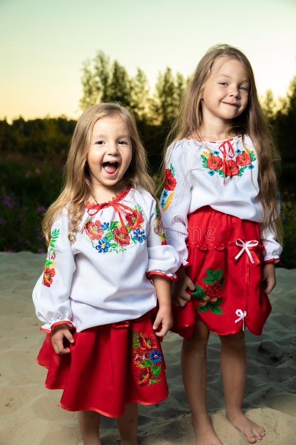 Two sisters in ethnic Ukrainian costumes in the meadow, portrait, friendship concept, children. royalty free stock photography