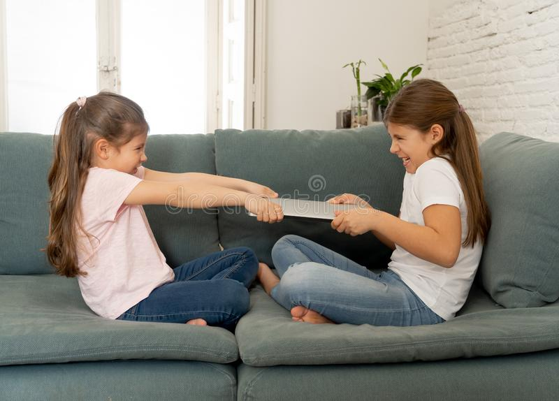 Two sisters fighting for laptop computer. Children and technology addiction royalty free stock photos