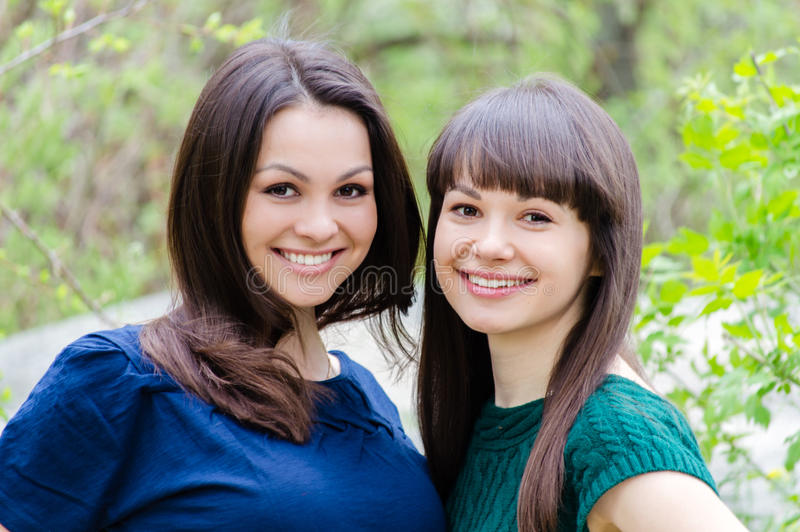 Two sisters or girl friends smiling, laughing and hug outdoors in spring or summer royalty free stock photo