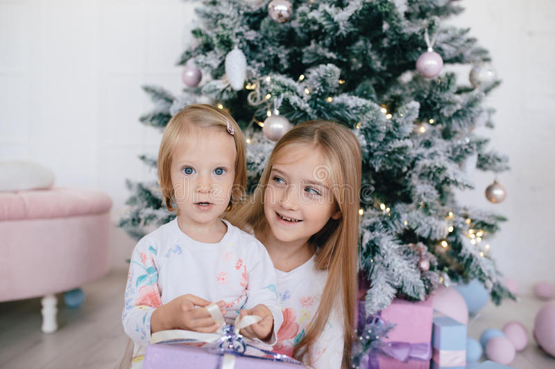Two sisters at home with Christmas tree and presents. Happy children girls with Christmas gift boxes and decorations. royalty free stock images