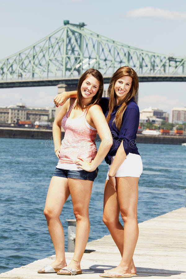 Two Sisters Interacting With Bridge Behind Stock Image