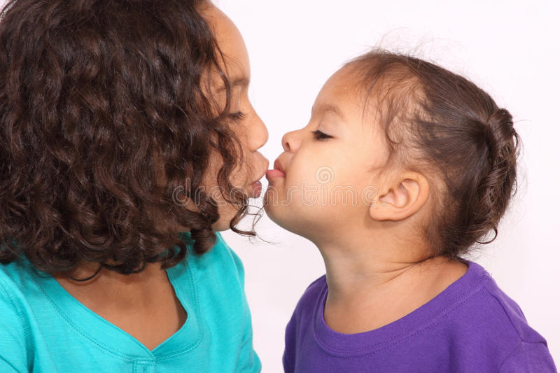 Two sisters kissing stock photos