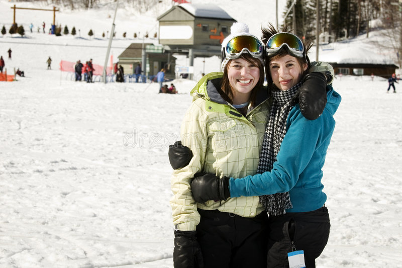 Two sisters in loving embrace. At ski resort stock photos