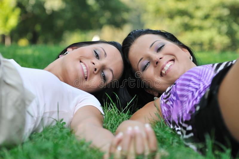 Two Sisters Lying Outdoors In Grass Holding Hands Royalty Free Stock Image