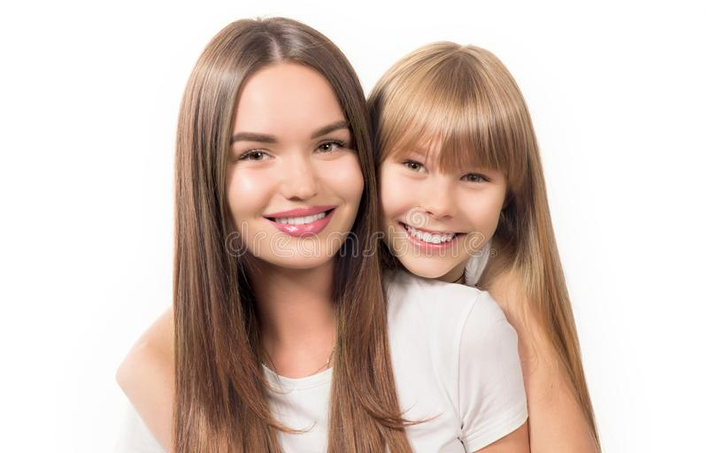 Two sisters - older and younger together. Portrait of beautiful young sisters teenage and adult girls hugging and smiling together. Isolated on white royalty free stock image