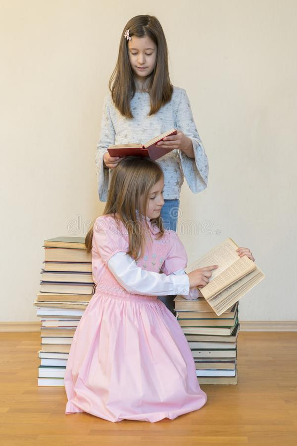 Two sisters with a pile of books on the floor in the room. The concept of education and development of children. Love of royalty free stock image