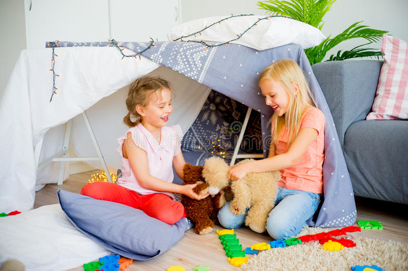 Two sisters in a play tent royalty free stock image