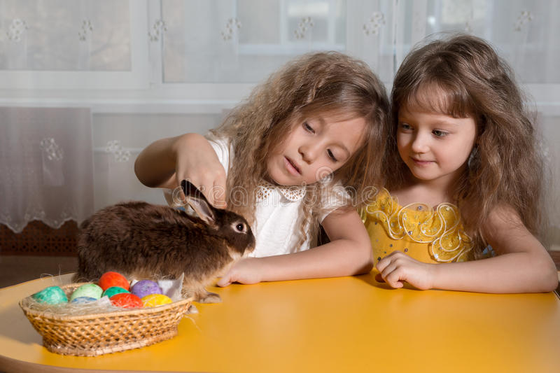 two sisters playing with the Easter Bunny royalty free stock photos