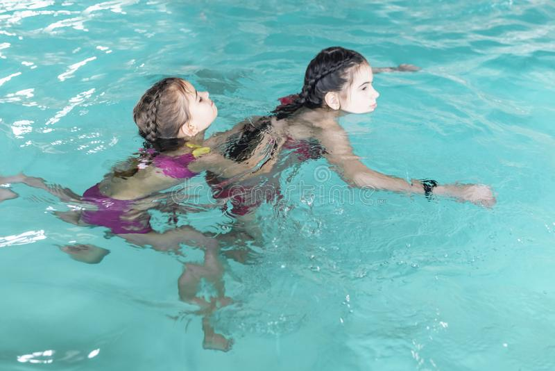 Two girls swim in the pool. Two sisters in the pool. Two happy girls play in the pool.Beautiful girls swim and having fun in water stock photos