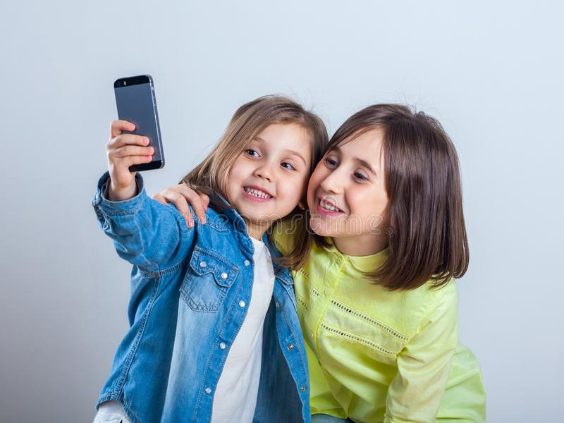 Two sisters posing and taking selfies in the studio stock image