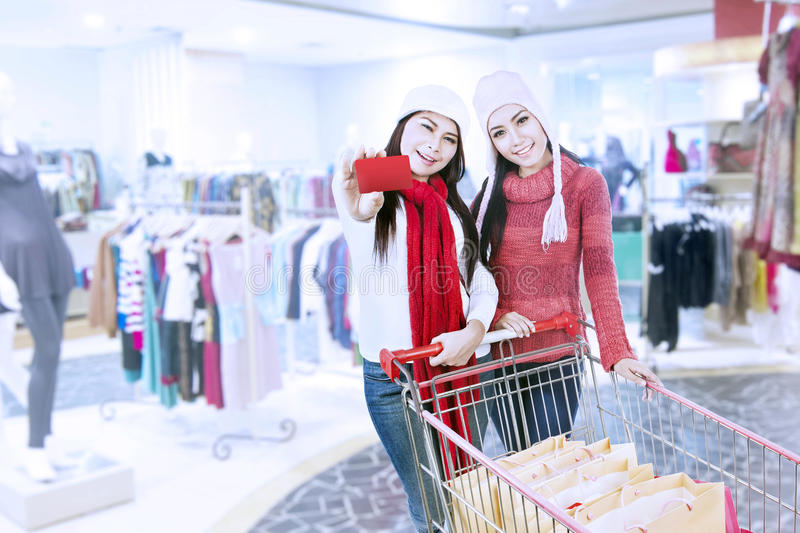 Two sisters shopping with gift card at mall. Two friends are shopping at the mall, while one of them showing a red gift card during winter time royalty free stock photos