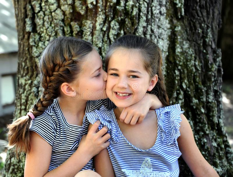 Affection Between Two Close Sisters. Two sisters sit outside besides a tree. They show their friendship and affection for each other by hugging and a soft kiss stock image