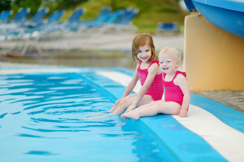 Two sisters sitting by a swimming pool. Two little sisters sitting by a swimming pool royalty free stock image
