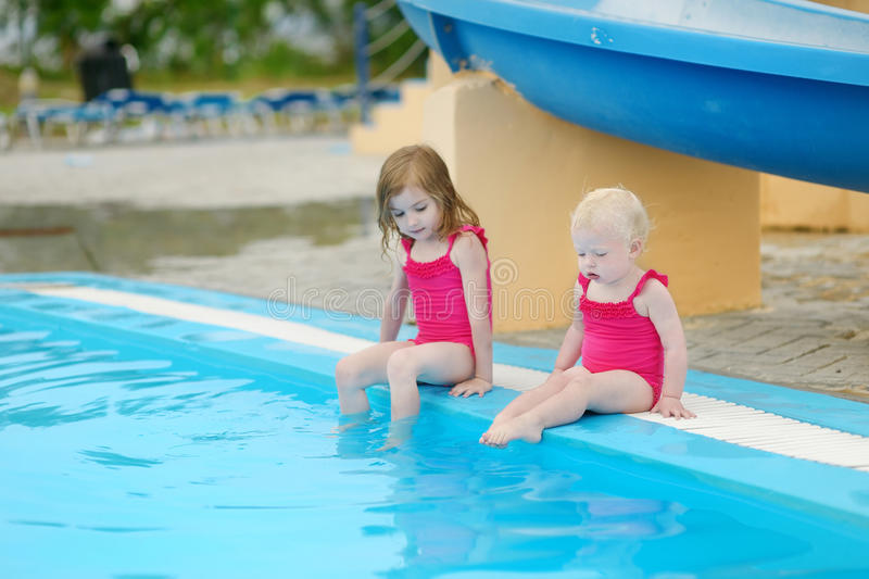 Two sisters sitting by a swimming pool. Two little sisters sitting by a swimming pool royalty free stock photo