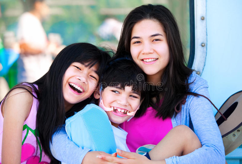 Two sisters taking care of disabled little brother royalty free stock photos
