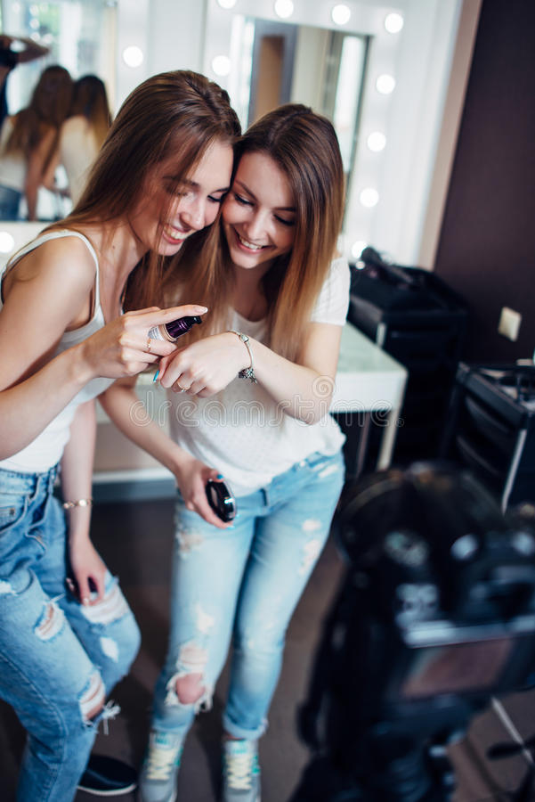 Two sisters testing foundation product cream recording a new make-up application guide for their beauty vlog stock photography