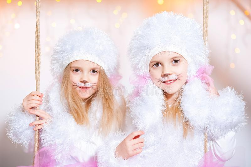 Two sisters twins in the costumes of dog poodles for the New Year. Makeup is like a dog. Portrait of a beautiful girl close-up on stock photos