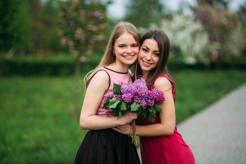 Two sisters walking outside in spring park. They hold a bouqet of lilac and smile.  royalty free stock image