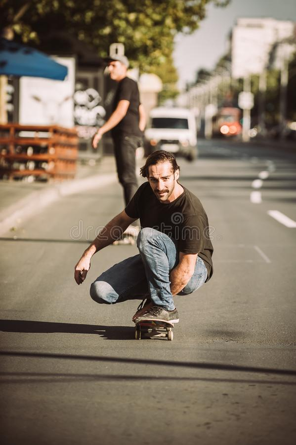 Two skateboarders ride a skateboard slope in the city street. Close up stock photo