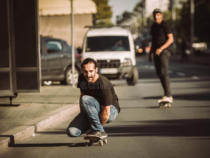 Two skateboarders ride a skateboard slope in the city street. Close up royalty free stock photos