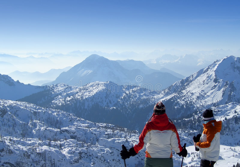 Two skiers looking over mountains top stock image