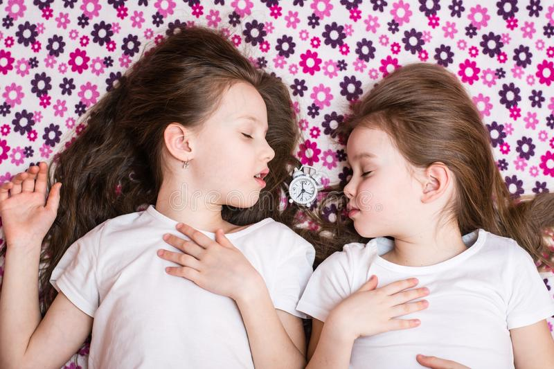 Two sleeping girls and a white alarm clock in between. Top view royalty free stock photos