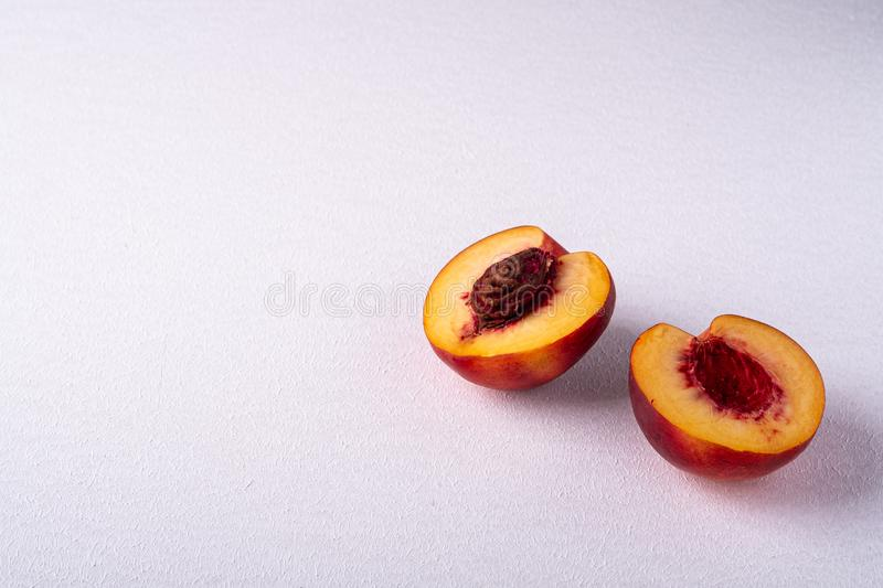 Two slice of peach nectarine fruit with seed on white background, copy space, angle view. Close up stock photos