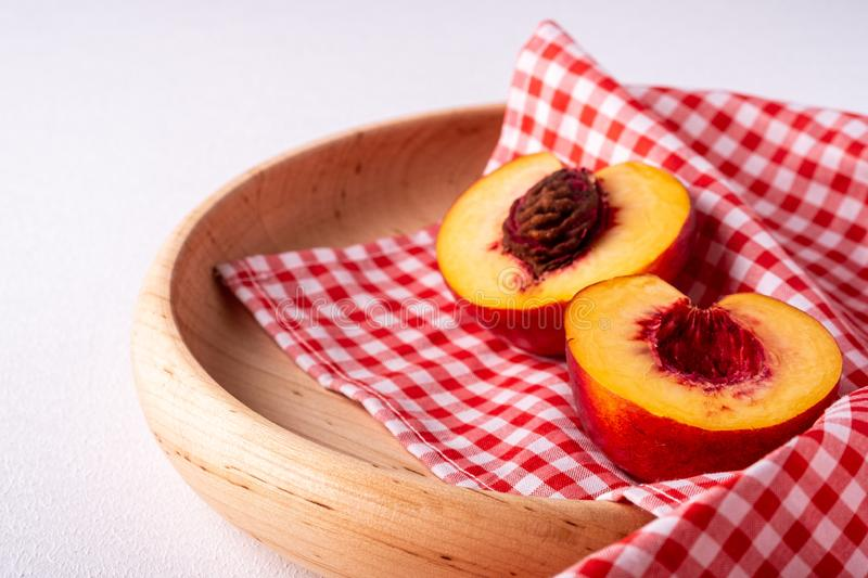 Two slice of peach nectarine fruit with seed in wooden plate with red checkered tablecloth on white background royalty free stock photography