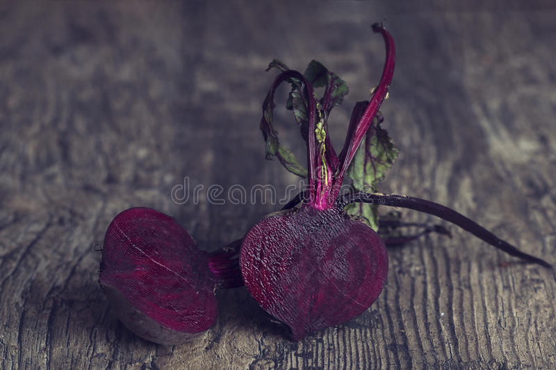 Two sliced beetroot on a brown wooden table in artistic conversion stock image