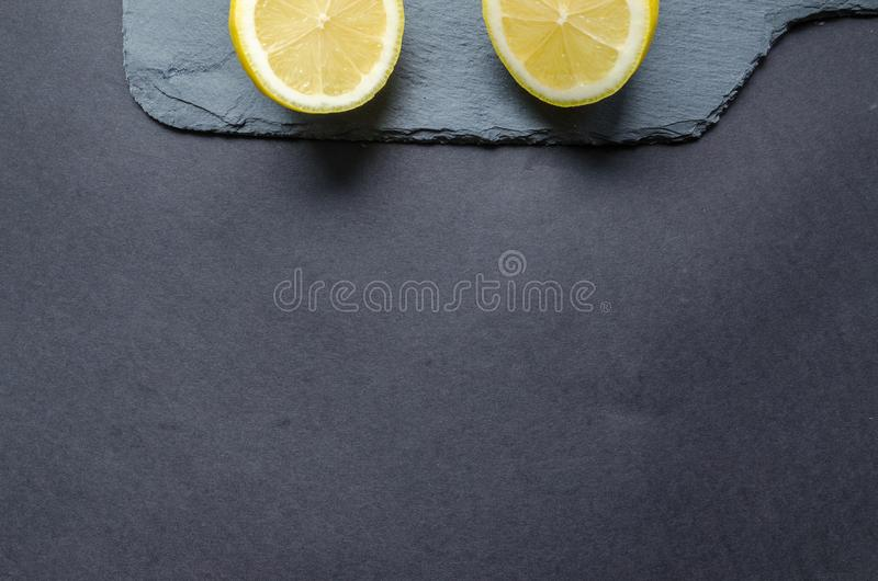 Two Sliced Lemons on Black Surface stock images