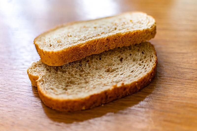 Two sliced slices of bran bread with a crisp crust of rye flour, lying on a brown wooden table, after fresh baking. In the kitchen in the sunlight stock photography