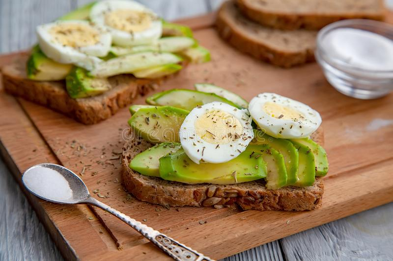 Two sliced ripe avocado sandwiches with egg and spices on a wooden Board. Top view. Healthy breakfast. Two sliced tasty avocado sandwiches with egg and spices on royalty free stock photo
