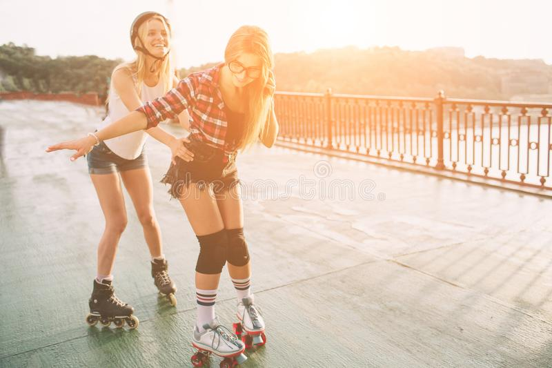 Two slim and young women and roller skates. One female has an inline skates and the other has a quad skates. Girls. Ride in the rays of the sun royalty free stock photo