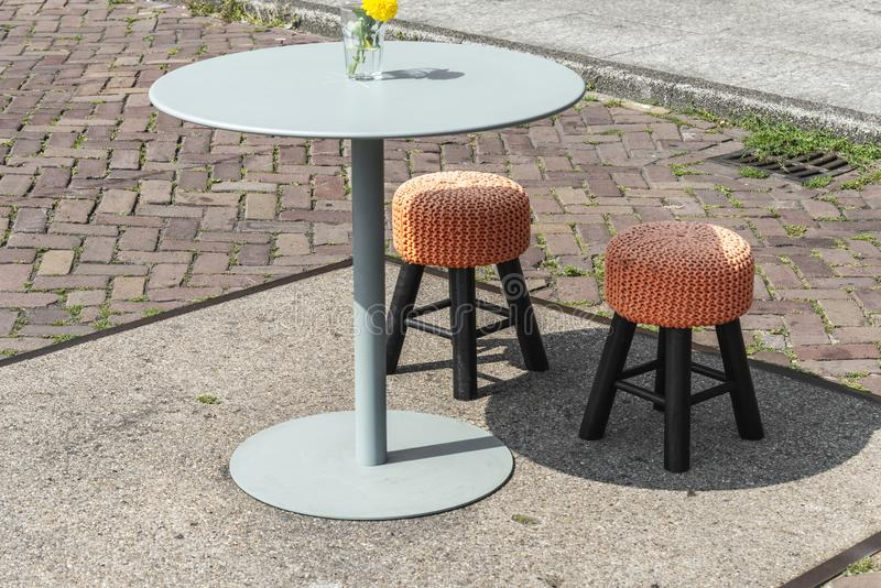 Two small bar stools with orange seats and a round table royalty free stock photo