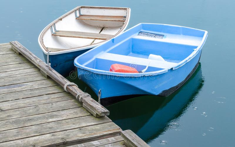 Two small rowboats tied to a wooden dock in Massachusetts stock images