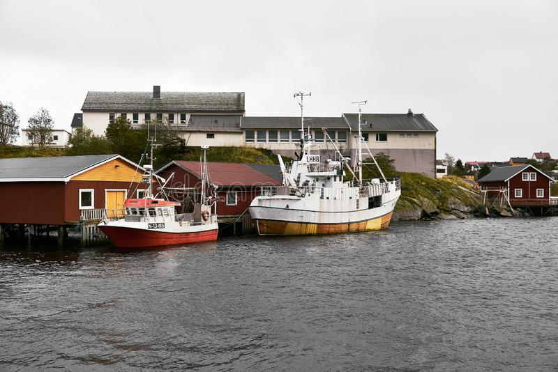 Two small boats at Reine harbor in front of traditional wooden fishing cabins on Lofoten Islands in Norway. royalty free stock photography