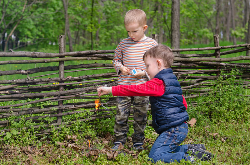 Two small boys lighting a fire in woodland. Setting fire to a pile of leaves and twigs in the grass as they enjoy a day camping in nature stock photo
