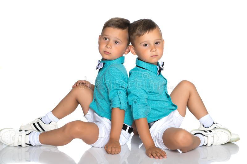 Two small boys sit on the floor back to back stock photography