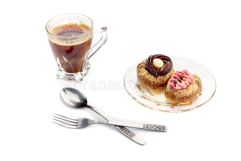 Two cakes and a cup of coffee. Two small cakes `roxakia` with syrup on a plate and a cup of coffee close-up against white background Greek cuisine stock images