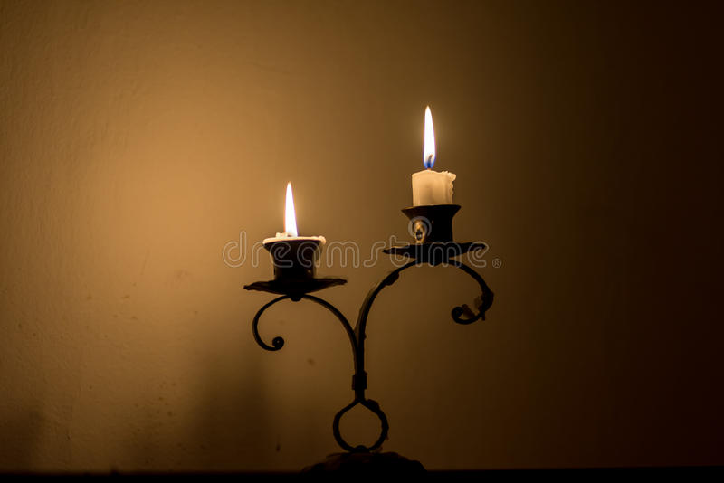 Two small candles on holder over melted wax, in dark. Romantic stock photo