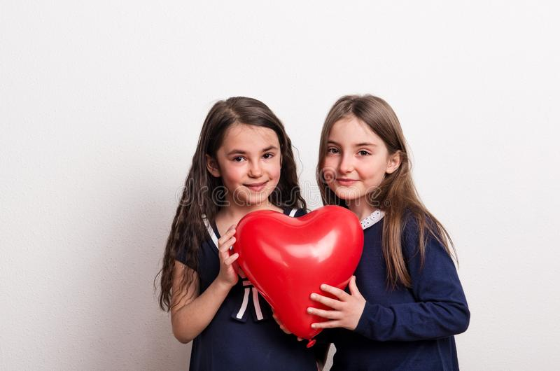 Two small girls in a studio, holding a red heart balloon in front of them. stock photos