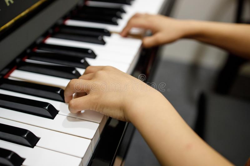 Two Small Childent`s Hands Playing The Piano stock photos