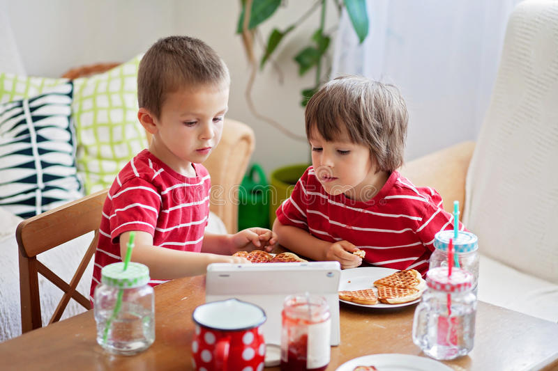 Two small children, boy brothers, eating breakfast at home, while watching cartoon. On tablet stock image